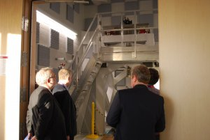Delegates looking at a piece of equipment in the RAC2 soundproof room