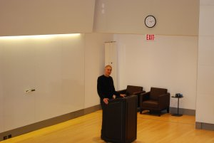 Dr. Dembo presenting at the front of the room, behind a black lectern.