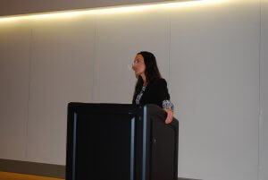 Tracey Forrest, presenting at the front of the room behind a black lectern.