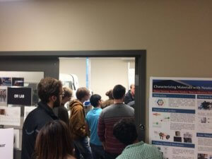 Open house attendees clustered together, looking at a research poster.