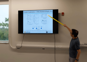 Information Session presenter pointing to a monitor with a stick.